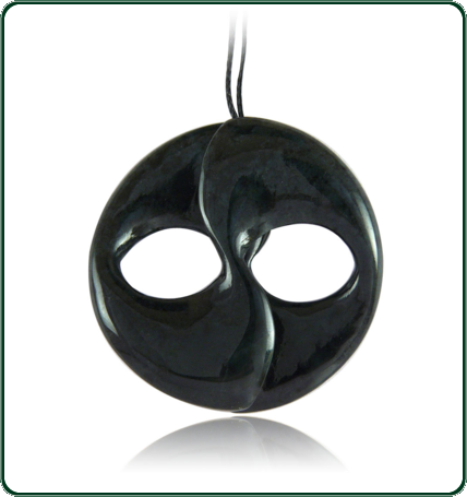 The flowing, organic lines of the dark jade medallion create a simultaneous impression of wide eyed innocence and deep wisdom.
